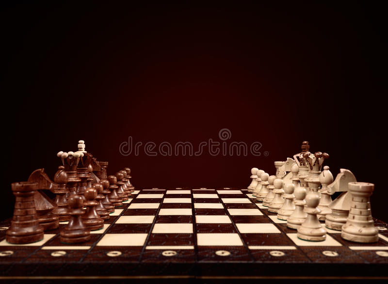 Chessboard. With chess pieces, board game on brown background stock photo