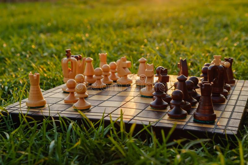 Chessboard and chess pieces on the grass in the garden. Hobbies and sports on vacation stock images