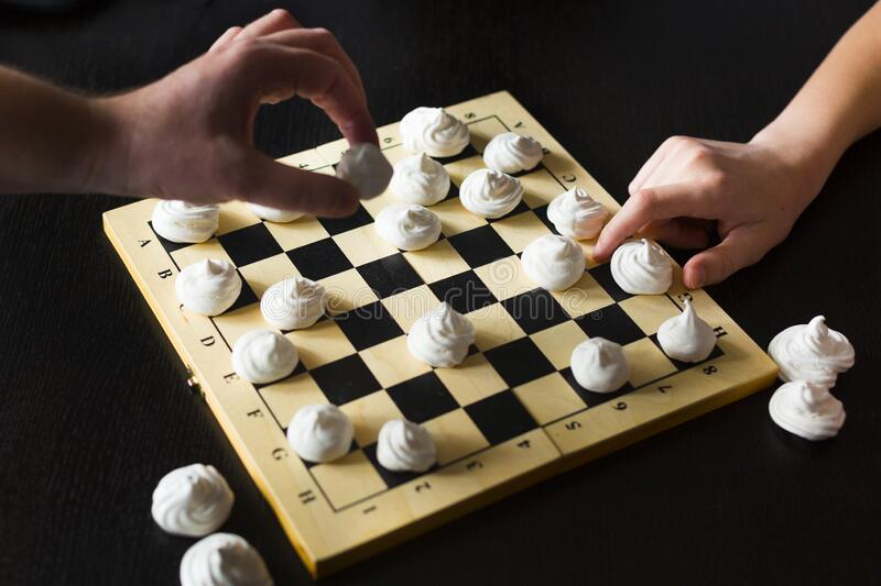 Chessboard com biscoitos brancos merengue em vez de xadrez imagens de stock