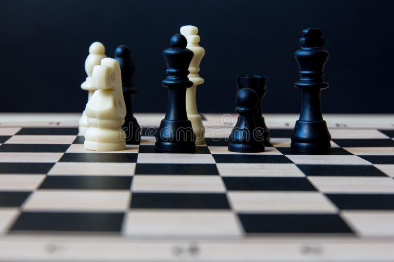 Chessboard with figures. Chess board with figures on a dark background. selective focus stock photography
