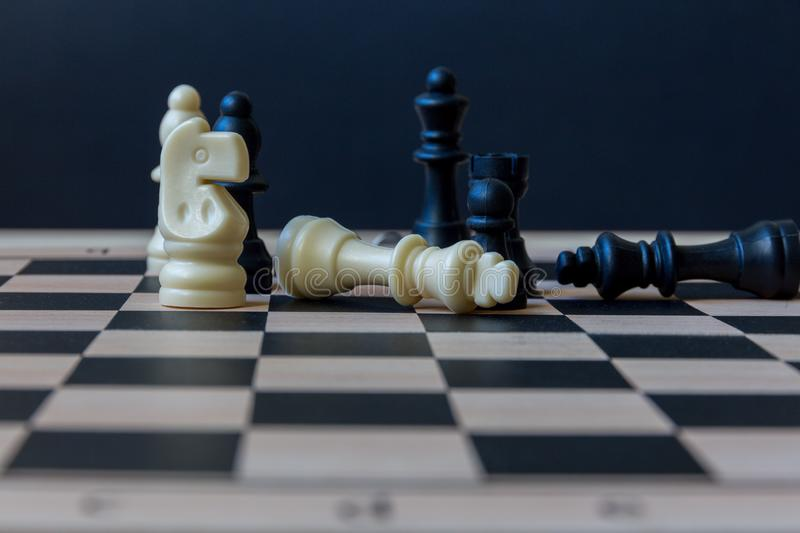Chessboard with figures. Chess board with figures on a dark background. selective focus stock image