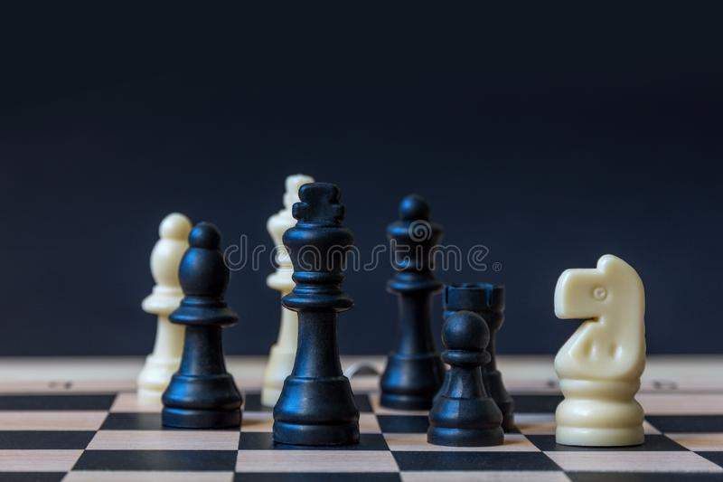 Chessboard with figures. Chess board with figures on a dark background. selective focus royalty free stock photography