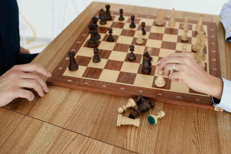 Chessboard is on the table. Hand is keeping chess figure royalty free stock photography