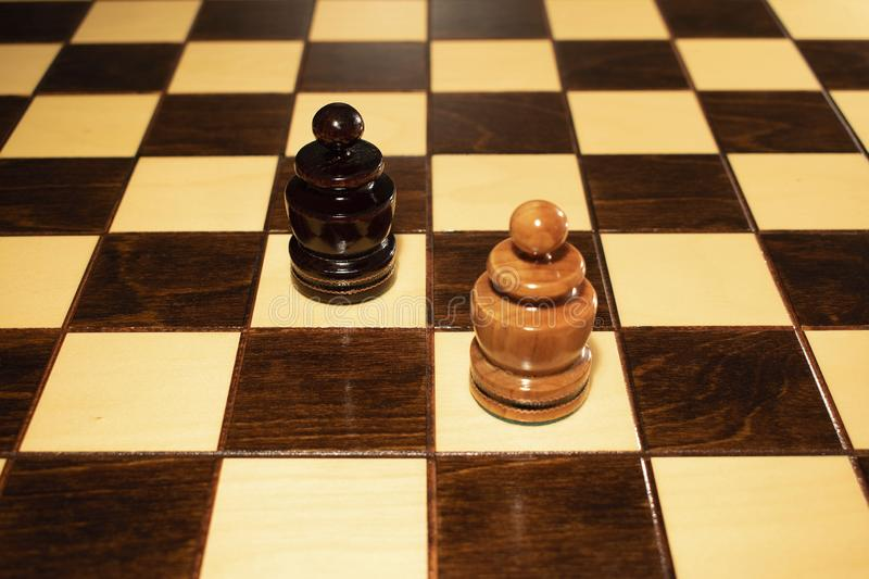 A chessboard with two opposing pawns stock photography