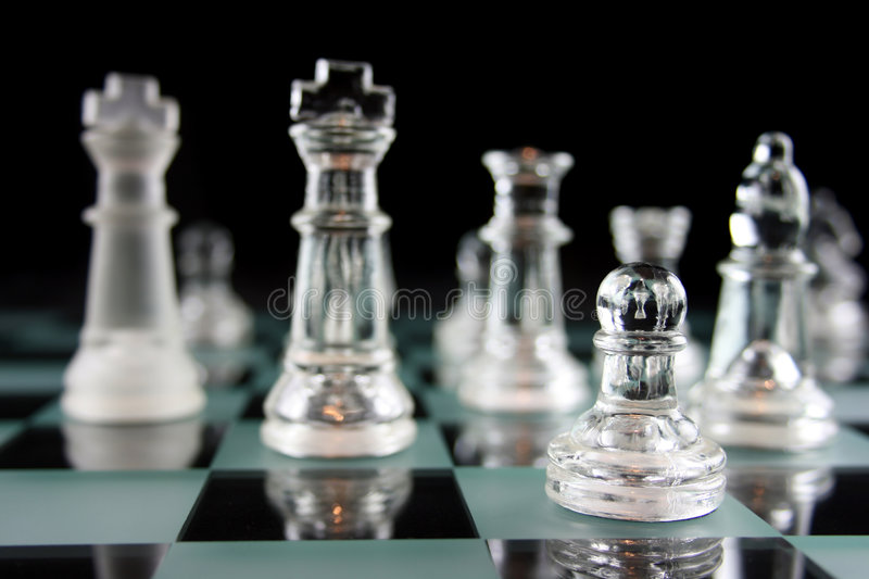 Chessgame - focus on the pawn. Glass Chess Pieces on a Frosted Glass Chess Board stock photography