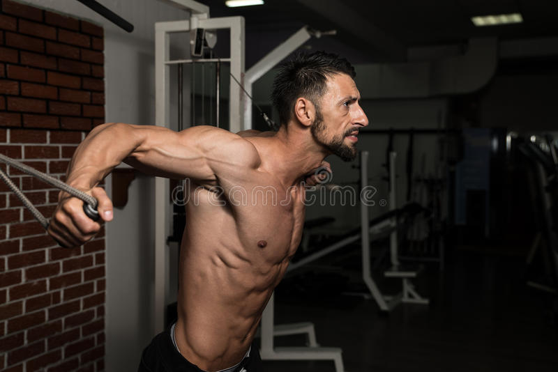 Chest Exercise. Bodybuilder Is Working On His Chest With Cable Crossover In A Dark Gym royalty free stock photos