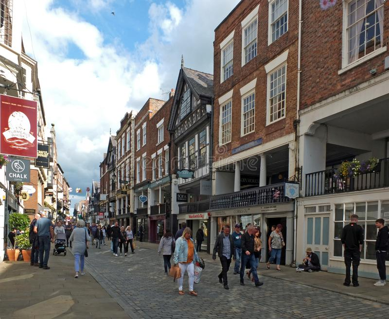 People walking along watergate street past pubs and shops in chester. Chester, cheshire, united kingdom - 7 september 2019: people walking along watergate street royalty free stock photo
