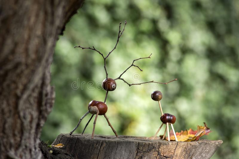 Chestnut animals on wooden stump, deer and female deer made of chestnuts, acorns and twigs, green background royalty free stock photos