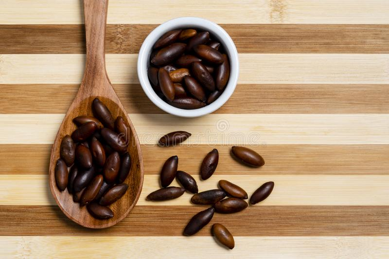 Chestnut Baru in wooden spoon and pot on bamboo striped table.  royalty free stock images