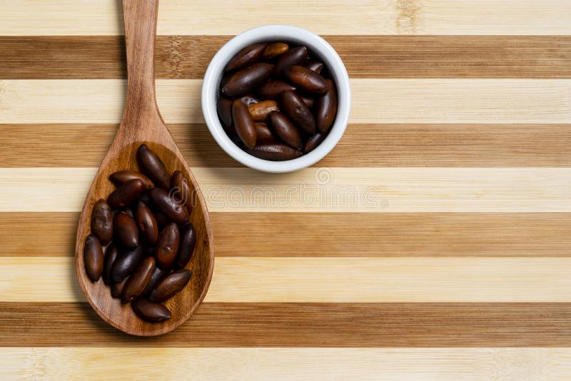 Chestnut Baru in wooden spoon and pot on bamboo striped table.  stock image