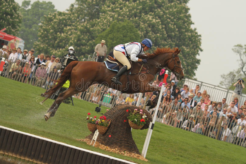 Chestnut horse and female rider jumping a fence. At the lake complex during the cross country phase of the Mitsubishi Badminton Horse Trials in 2011 royalty free stock photos