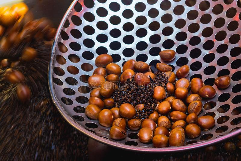 Chestnut roasting with black pebble. Traditional asian street food cooked in Yaowarat Road or China town, Bangkok ,Thailand. Background brown business chestnuts stock image