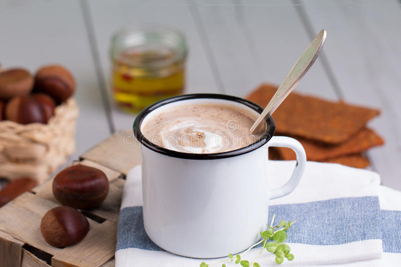 Chestnut soup in white enamel mug with roasted chestnuts royalty free stock photography