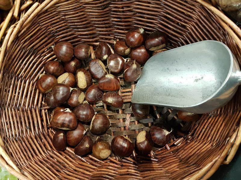Chestnuts in the basket bailer in market place food background. Colors stock images