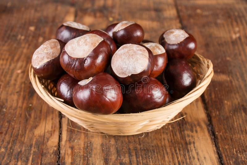 Chestnuts in beautiful retro basket on wooden desk stock photos