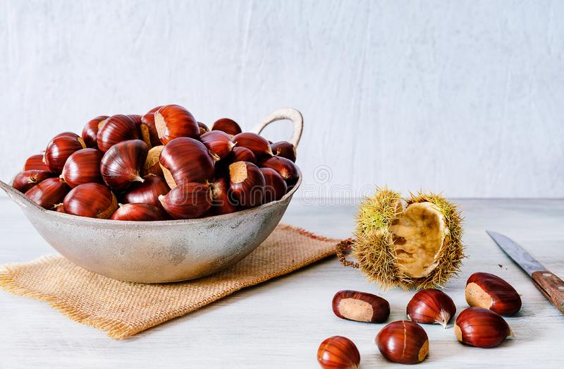 Chestnuts in a metallic basket on rustic wooden background royalty free stock photos