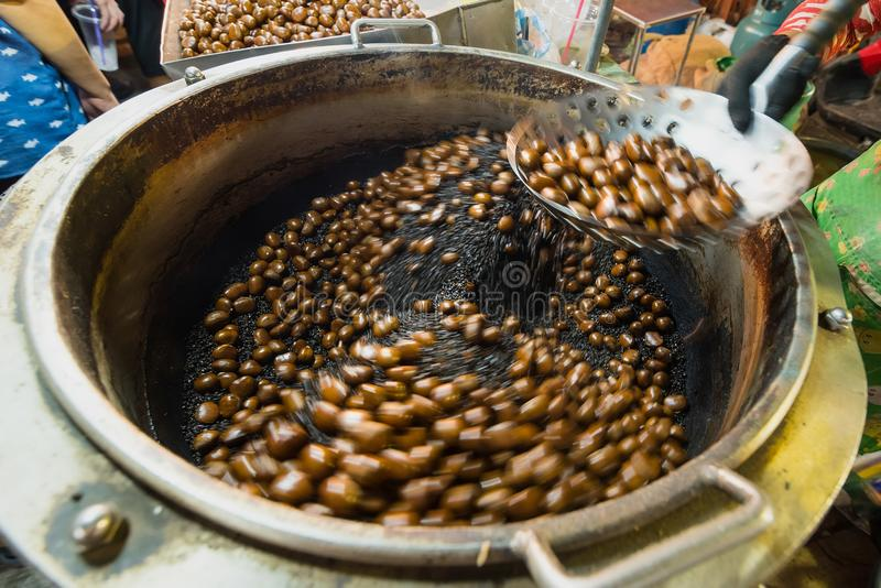Chestnuts roasted with coffee beans on the fire from a street vendor with spin fry pan. Group of blurry edible ripe chestnuts due. To spinning effects royalty free stock photo