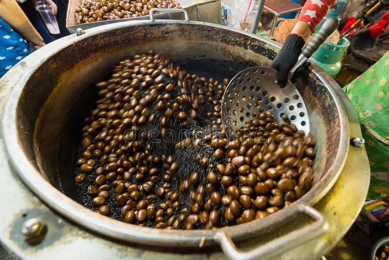 Chestnuts roasted with coffee beans on the fire from a street vendor with spin fry pan. Group of blurry edible ripe chestnuts due royalty free stock photos