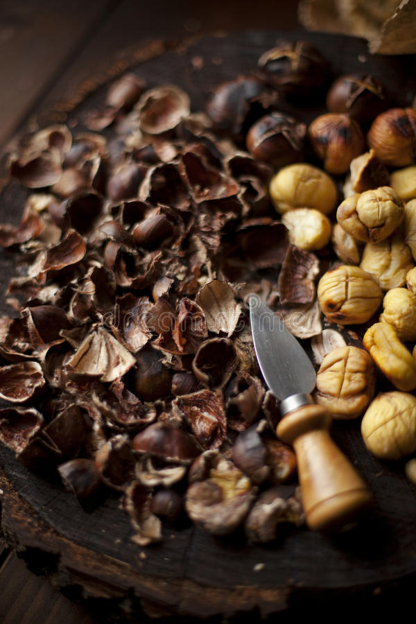 Chestnuts Roasted and Peeled on a Wooden Slab. Detailed view of peeled and roasted chestnuts on a wooden slab with a little knife stock photography