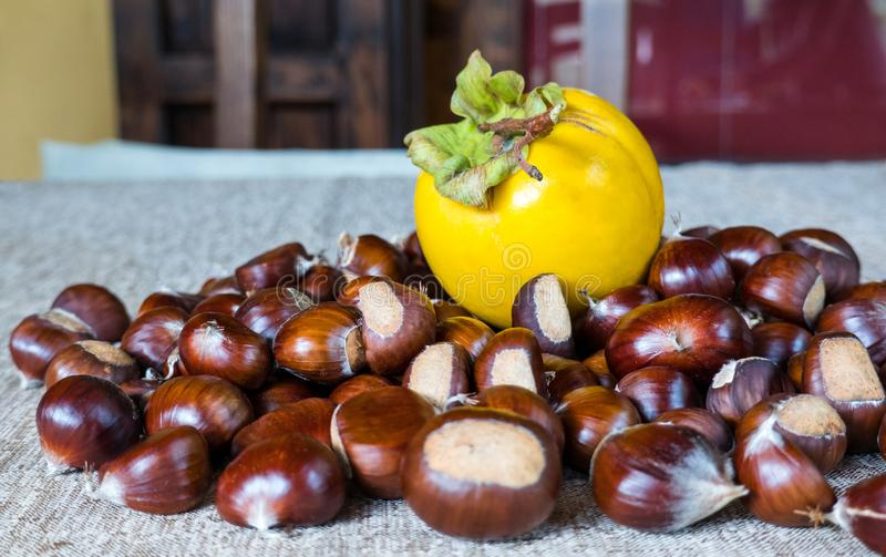 Chestnuts on a rustic tablecloth, outside, with a yellow Persimmon stock photo