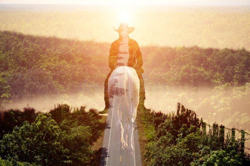 Cheval d'équitation de cowboy de double exposition sur les économies du monde d'économies de route images stock