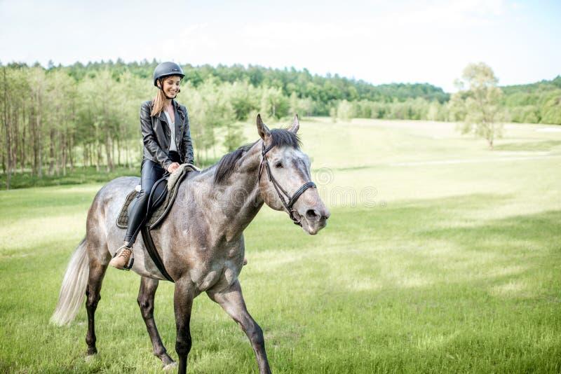 Cheval d'équitation de femme sur le pré vert image libre de droits