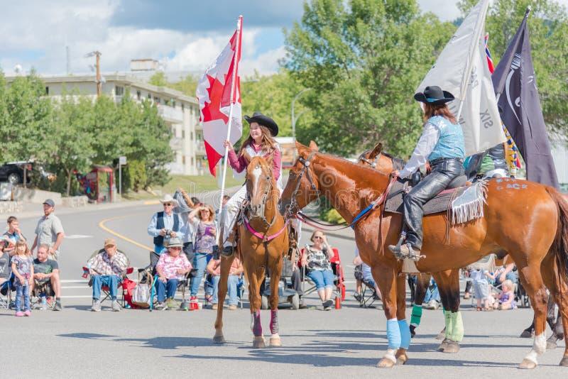 Cheval d'équitation de fille et drapeau canadien de participation au défilé photographie stock