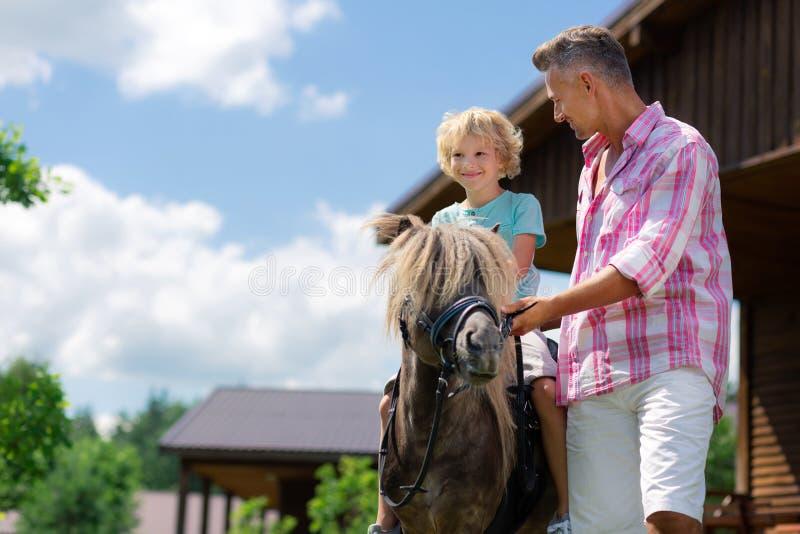 Cheval d'équitation heureux de sentiment bouclé aux yeux noirs de fils pour la première fois image stock
