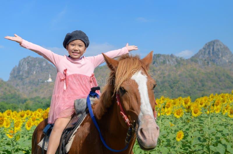 Cheval d'équitation mignon heureux de fille dans le domaine de tournesol photo stock