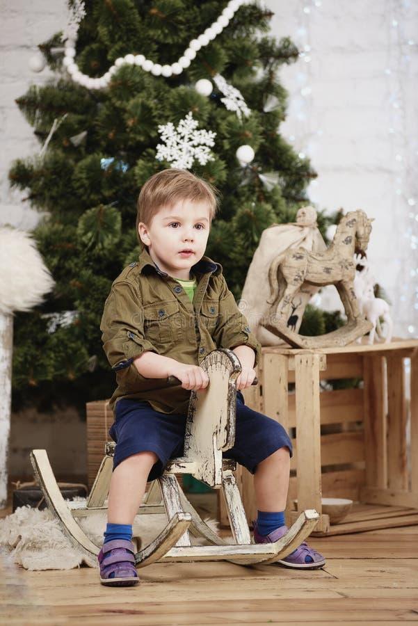 Cheval de basculage en bois de petit tour de garçon devant l'arbre de Noël photos libres de droits