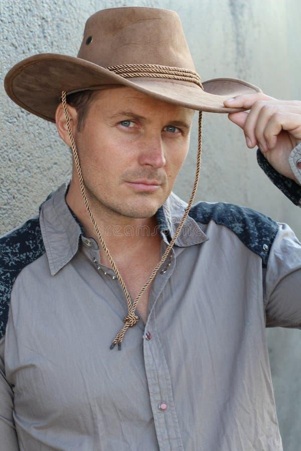 Chevaleresk gentleman i cowboydräkten som tippar hans hatt royaltyfria bilder
