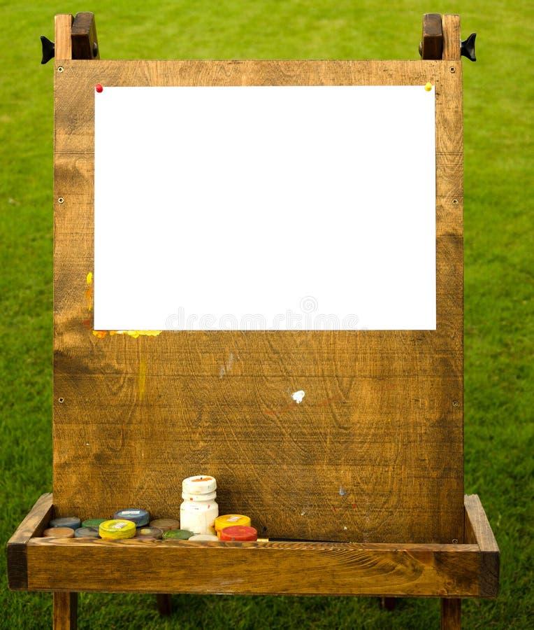 Chevalet en bois avec le livre blanc sur l'herbe photo stock
