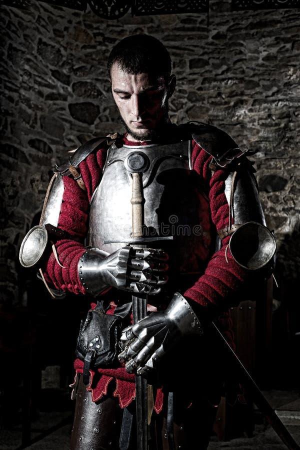 Chevalier courageux Standing With Head cintré la prière et en tenant l'épée en métal contre le mur en pierre photos stock