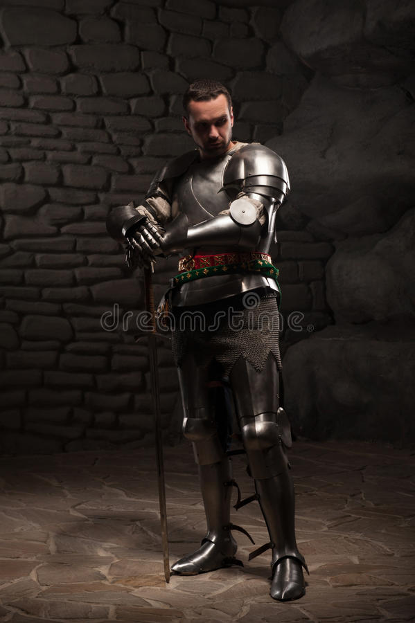 Chevalier médiéval posant avec l'épée dans une pierre foncée photo stock