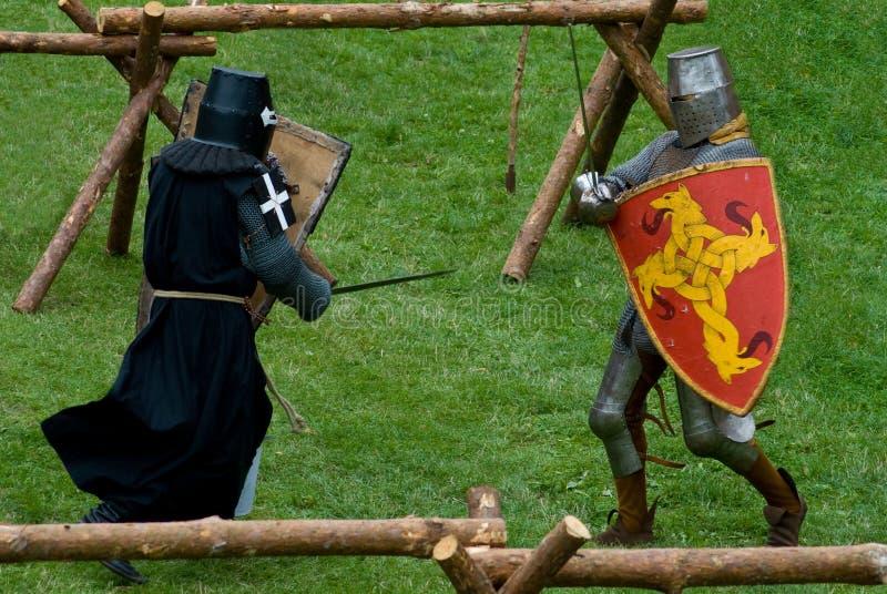 Chevaliers aux pieds médiévaux, combat photos stock