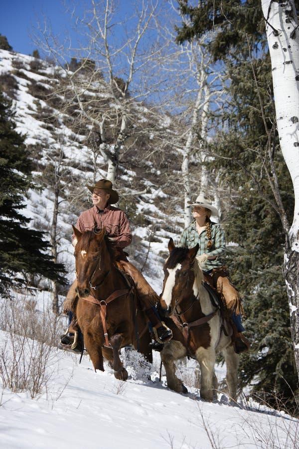 Chevaux d'équitation d'homme et de femme dans la neige photo libre de droits