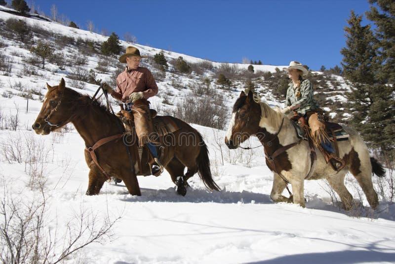 Chevaux d'équitation d'homme et de femme dans la neige image libre de droits