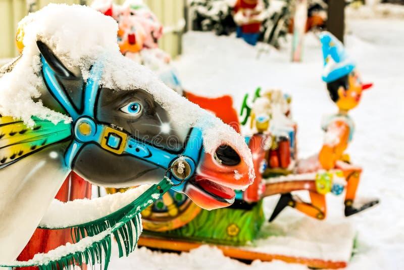 Chevaux d'équitation dans les ronds points en parc de ville d'hiver photos libres de droits