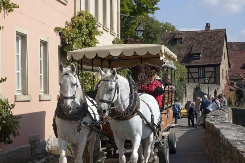 Chevaux et chariot en visite guidée avec les maisons bien préservées à l'arrière-plan images libres de droits