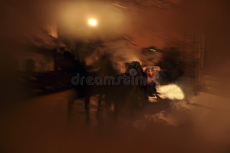 Chevaux noirs de Noël féerique devant maison en bois décorative avec des lumières à l'intérieur sur le fond noir avec la lune, sa image libre de droits