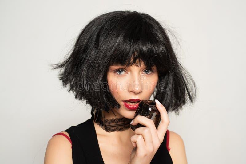 cheveu artificiel Coiffeur et coiffure Madame dans la perruque noire avec composent Soins capillaires et dénommer Salon de coiffe photos libres de droits