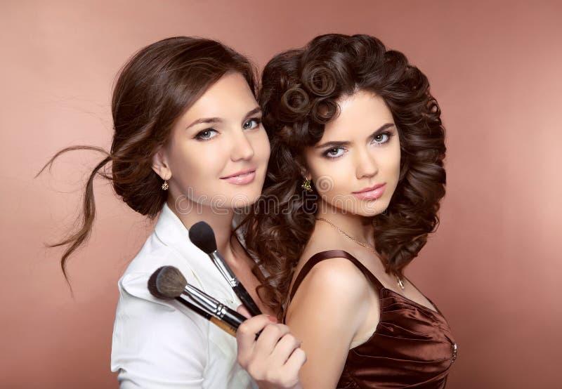 cheveu Belles deux filles de sourire de brune Maquilleur avec b image stock