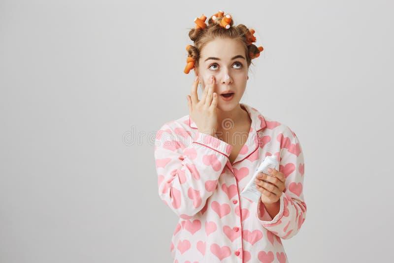 Cheveu-bigoudis de port et pyjamas de fille européenne féminine mignonne appliquant la crème sur la peau propre, recherchant et s photographie stock