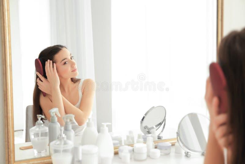 Cheveu de brossage de jeune femme devant le miroir image stock