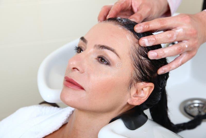 Cheveu de lavage de femme dans le regroupement de salon photo libre de droits