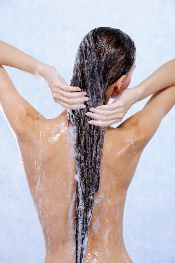 cheveu femelle sa douche prenant le lavage photo libre de droits