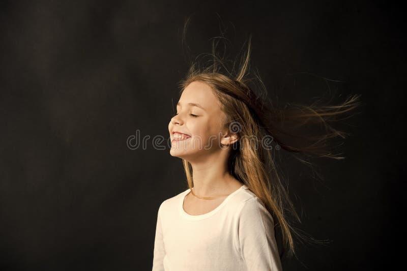 Cheveu normal Vol de cheveux d'enfant de fille long en air, fond noir Enfant avec la belle coiffure saine naturelle images stock