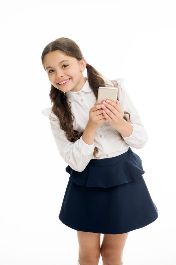 Cheveux bouclés mignons de fille les longs tiennent le fond de blanc de smartphone La fille d'enfant que l'uniforme scolaire vêtx images stock