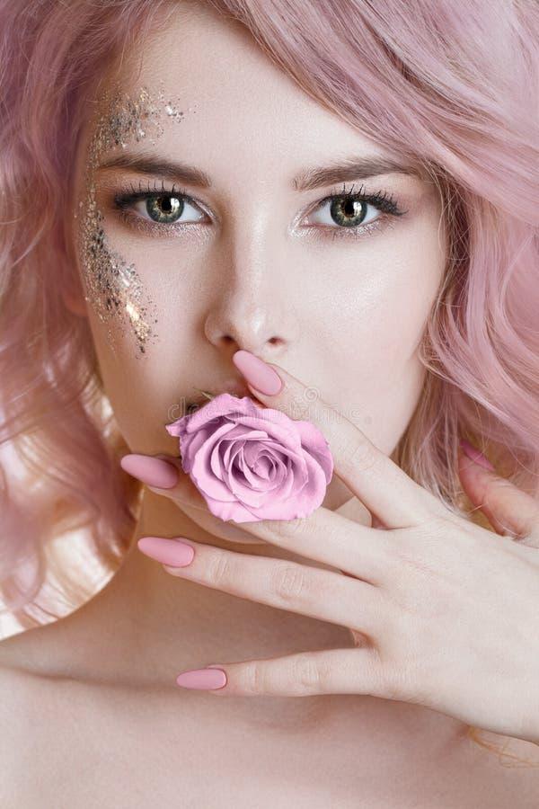 Cheveux colorés Le portrait de femmes de beauté de la jeune femme bouclée avec le pastel rose a coloré les poils, la manucure et  images stock