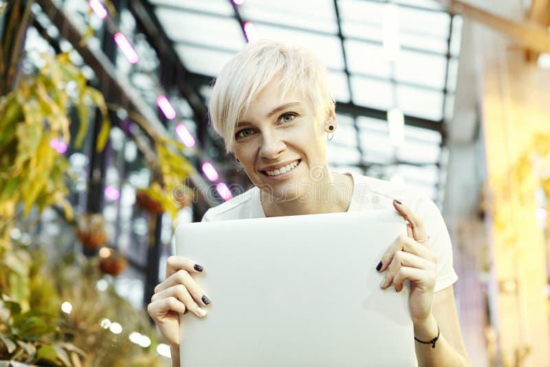Cheveux courts blonds de belle femme moderne souriant avec l'ordinateur portable dans des mains Heureux avec le démarrage, se rep images libres de droits